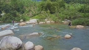 Drone Shows Guy Stepping on Stones Man Taking Net from River stock footage