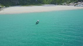 Drone shows boat on azure ocean by white sand beach. Drone shows blue boat on shallow turquoise ocean by empty white sand beach among green rocky hills stock video footage