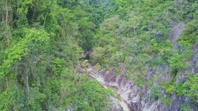 Drone Shows Creek Streaming into Lake against Rocky Jungle. Drone moves down and shows powerful creek streaming into transparent lake against rocky jungle stock footage