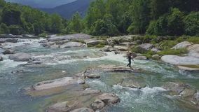 Drone Shows Guy Throwing Fishing Net into River among Stones stock video footage