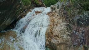Drone Shows Waterfall Streaming against Rocks Background stock video footage