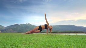 Drone Side View Girl Holds Yoga Position against Green Hills stock video footage