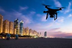 Drone silhouette flying above Dubai city panorama Stock Photos