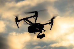 Drone silhouette flying in the evening sky Stock Images