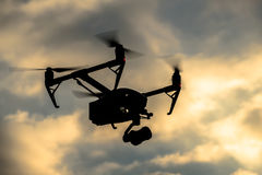Drone silhouette flying in the evening sky Stock Photo