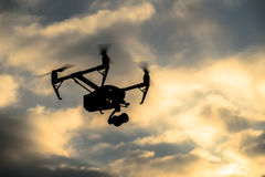 Drone silhouette flying in the evening sky Stock Image