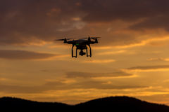 Drone silhouette flying in sunset landscape Stock Images