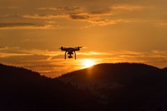 Drone silhouette flying in sunset landscape Stock Photos