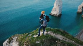 Drone spins close around young happy tourist couple standing together on top of famous Normandy sunset white coast cliff. Drone spins close around young happy stock video footage