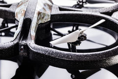 Drone spy system. Detail shot of a small camouflaged quad copter spy drone over a black reflective surface royalty free stock image
