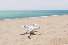 Drone standing on a sandy, bright beach in the sunshíne. White drone on a waste beach standing in the sunshine, clear to lift off Royalty Free Stock Photography