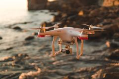The drone in the sunset sky. ocean wave mountains Close up of quadrocopter outdoors. concept for film maker wedding videography. Aerial photographer. equipment stock photo
