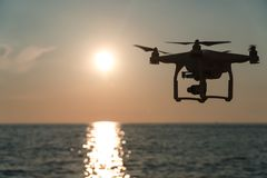 The drone in the sunset sky. ocean wave mountains Close up of quadrocopter outdoors. concept for film maker wedding videography. Aerial photographer. equipment stock image