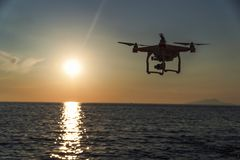 The drone in the sunset sky. ocean wave mountains Close up of quadrocopter outdoors. concept for film maker wedding videography. Aerial photographer. equipment royalty free stock photo