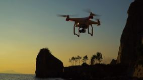 The drone in the sunset sky. ocean wave mountains Close up of quadrocopter outdoors. concept for film maker wedding videography stock video
