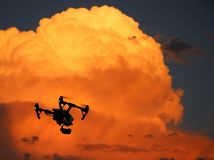 Drone with Surveillance Camera. A silhouette of a drone with a surveillance camera that is hovering in a red sky stock photo