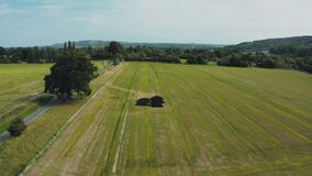 Drone take off from farm land over treetops looking at rural countryside during hot sunny day in September, UK