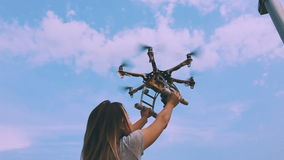 Drone takes off from the hands of a girl near a wind turbine, slow motion. stock video footage