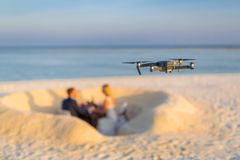 Drone taking footage and images of wedding couple at the beach. Beach scene with wedding couple blurred in the background. Drone taking footage and photos Royalty Free Stock Photography