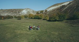 Drone taking video from air a big company of friends have a trip together at nature they happy walking together. stock video