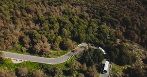 Drone tilts down on mountain road and vehicles. Aerial view of amazing summer serpentine with bus, van and two cars. 4K. Drone tilts down on busy mountain road stock footage