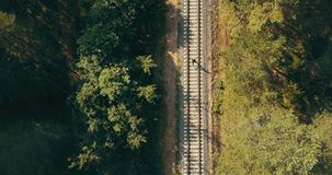 Drone top view of man running on train track. Concept of life never ending journey. Chasing dreams and surviving. Drone top view of athlete running on train stock video footage