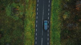 Drone top view camera tracking black car driving on empty highway along cloudy autumn forest on atmospheric road trip.
