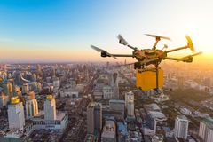Drone transport flying with cardboard box above city. Futuristic delivery concept royalty free stock image