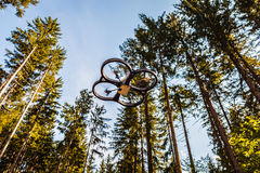 Drone and trees. A small spy quad copter scout drone flying through the trees in a forest royalty free stock images