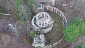 Drone view of abandoned restaurant on Mount Akhun, Sochi, Russia. Drone view of the abandoned building of the former restaurant among the trees on the top of stock video footage