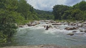 Drone View Fisher Drops Net into Shallow River among Rapids stock video footage