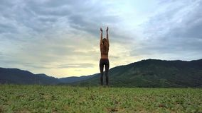 Drone View Girl Stands in Yoga Pose against Hilly Landscape stock footage