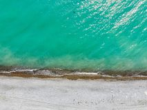 Aerial top view of beach and turqouise water for natural backgroud. Drone view of bright ocean water and empty sandy beach stock photography