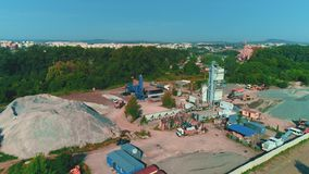 Aerial view of large sand piles and launching of building. 4K. Drone view of concrete factory territory and nearby facilities and one person ruling the process stock video