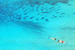 Drone view of couple snorkeling in clear blue sea water Royalty Free Stock Photography
