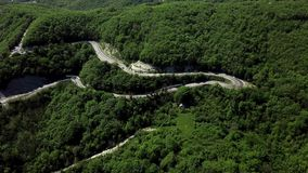 Drone view of a curved winding road trough the mountains stock footage