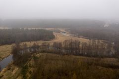 Drone view of curving river, forest and fog in rural landscape royalty free stock image