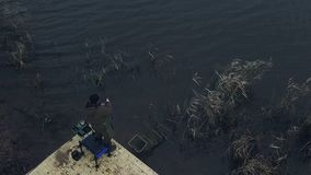 Drone view fisherman spinning fishing reel during biting on background river. Drone view fisherman spinning fishing reel during biting on background autumn river stock video
