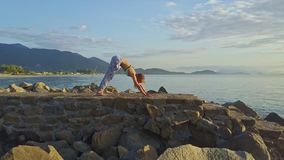 Drone view girl does yoga against tranquil sea hills stock video footage
