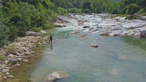 Drone View Guy Stands on River Bank Throws Net against Rapids stock video footage
