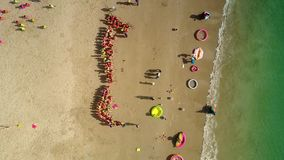 Kids spend leisure on seacoast playing games. Drone view little kids spend leisure on seacoast playing games under sunshine in front of wavesurf stock video