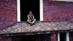 Drone view military soldier sitting on roof destroyed building in cottage village. During military operations. Military man on background abandoned houses in stock video