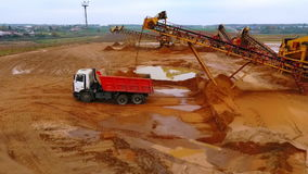 Drone view of mining conveyor pour sand in dumper truck. Mining machinery. Mining conveyor pour sand in dumper truck. Mining conveyor belt working at sand mine stock video footage