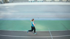 Drone view of overweight woman running along track. Aerial side view of slimming plus size female jogging during morning fitness workout on city stadium track stock footage