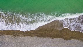 Drone view of seacoast. Top-down drone view of the seacoast with the surf and the pebble beach stock photo