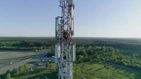 Drone view of telecommunication antenna system technician man dressed in uniform and helmet working on top stock video