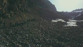 Drone view tourist group hiking mountain valley. Tourists on mountains trail. Drone view tourist group hiking mountain valley. Hiking group climbing a mountain stock footage