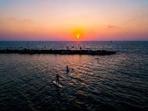 SUP surfers paddling with sunset royalty free stock images