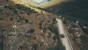 Drone view truck car driving along winding road mountain at sumer day. Drone view truck driving along winding road mountain. View from above truck car moving on stock footage