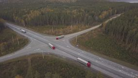 Drone view truck car with freight container across road junction on highway. On background autumn forest. Freight truck moving on cross roads on suburban stock footage
